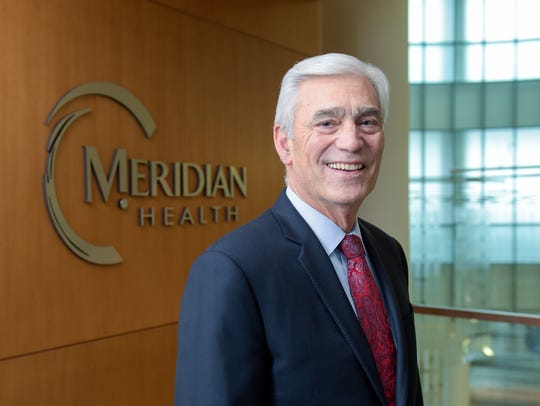 John Lloyd, president and CEO of Meridian Health, stands