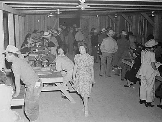 Evacuees of Japanese ancestry register upon arrival at War Relocation Authority centers in Poston, Arizona where they will spend the duration on May 28, 1942.