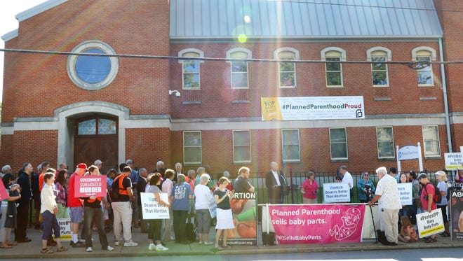 Protesters in August near the Planned Parenthood in Mount Auburn. The state has moved to deny the abortion clinic's license, but a federal judge says it must stay open during its appeal.