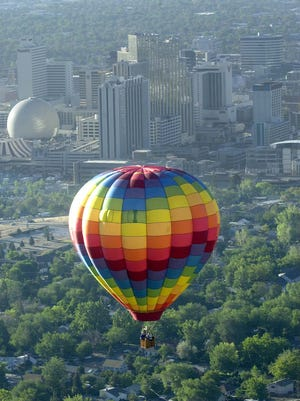 A balloon floats by the Reno skyline during the warm-ups for the Great Reno Balloon Race.
