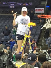 Livonia native and Dearborn Divine Child grad Maureen Butler cuts down a piece of the NCAA Championship net after Notre Dame's 61-58 win over Mississippi State.