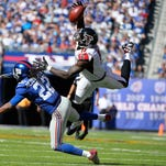 Julio Jones of the Falcons makes a first down reception in the fourth quarter under pressure from Brandon Meriweather of the GiantsThe Falcons defeated the Giants 24-20.