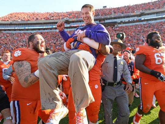 Clemson head coach Dabo Swinney is hoisted up by offensive tackle Isaiah Battle (79) as time expired in the Tigers 35-17 win over South Carolina Saturday, November 29, 2014 at Clemson's Memorial Stadium. Also celebrating with Dabo is offensive guard Spencer Region (74)
