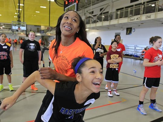 Tamika Catchings laughs and plays with her cousin,