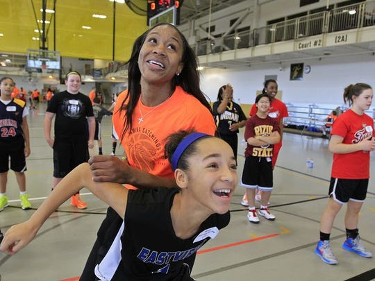 Tamika Catchings laughs and plays with her cousin, 11-year-old Kiree Catchings-Murray, during the Tamika Catchings' Catch the Stars Foundation 13th Annual Youth Holiday Basketball Camp at Warren Central High School in 2013.