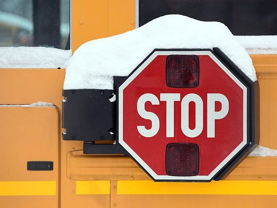A school bus stop sign, covered in snow