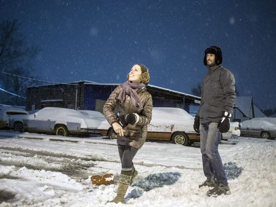 Heather Bowersox throws a snowball while friend Matt Shepard looks on during the snowstorm in West Asheville early Thursday morning.
