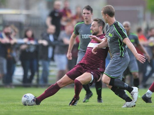 Detroit City's David Edwardson pokes the ball away from Muskegon's midfielders, including Alexi Munro, in the first half Saturday. DCFC won, 3-1.