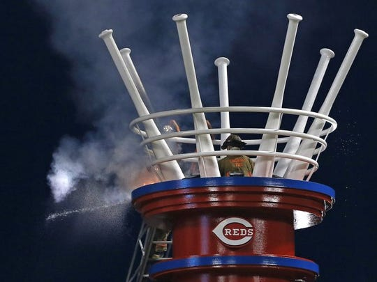 Cincinnati firefighters extinguish a fire at the top of the PNC Power Stacks following a pyrotechnics malfunction during the bottom of the sixth inning of the MLB game between the Cincinnati Reds and the San Francisco Giants at Great American Ballpark in Cincinnati, on Friday, May 15.