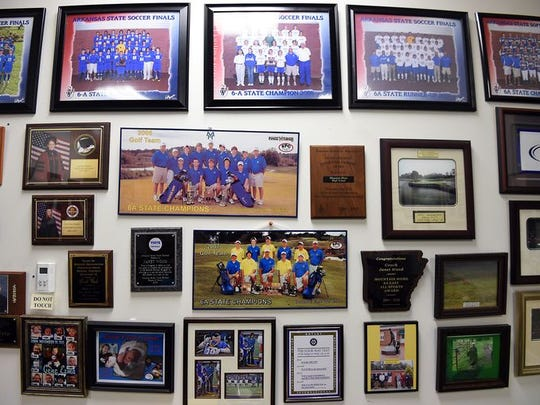 Photographs of a number of school championships hang on the wall in Janet Wood's office.