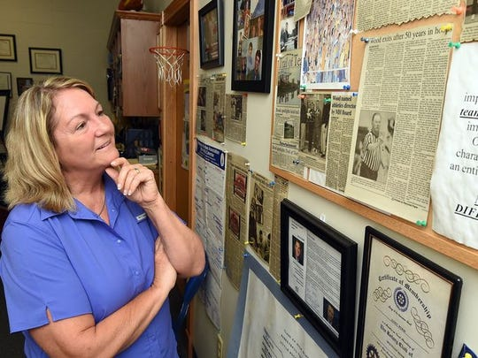 Janet Wood looks over memorabilia in her office. After 34 years with the Mountain Home School District, all but five with the athletic department, Wood is now taking a new position with the district as Research and Development Specialist.