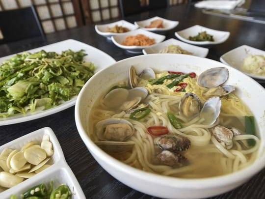 A steaming-hot bowl of Japanese-style udon noodles with a Korean-seasoned little-neck clam soup is ready to eat at Mi Dahm restaurant in Upper Tumon.