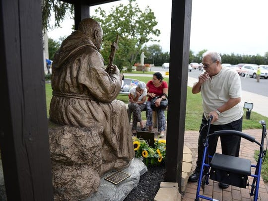 People pray to a Padre Pio statue in Vineland.