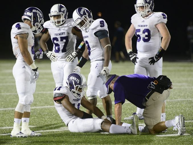 Fremont Ross' Jarren Hampton is attended to by trainer Joe Hersey during the Little Giants' 45-28 loss at St. John's last week.