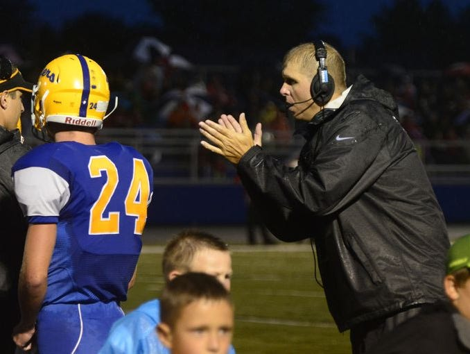 Clyde football coach Ryan Carter claps for his team from the sideline in the Fliers' Week 3 win over Bellevue.