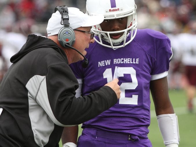 New Rochelle quarterback Greg Powell has a chat with Coach Lou DiRienzo as they play Arlington in a Section One Class AA semifinal game at New Rochelle High School, Nov. 1, 2014. New Rochelle lost to Arlington, 23-20.