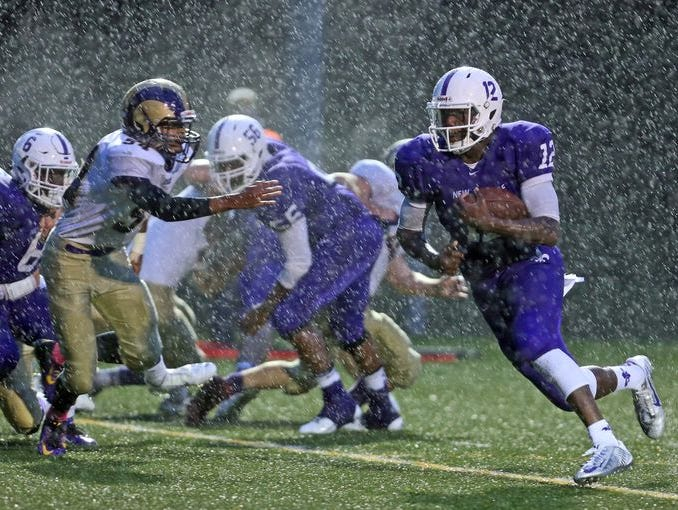 New Rochelle quarterback Greg Powell rushes through the rain for New Rochelle's first touchdown against Clarkstown North at during a varsity football game at New Rochelle Oct. 2, 2015. New Rochelle defeated Clarkstown North 12-6.