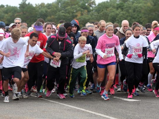 Runners burst from the starting line of the Susan G.