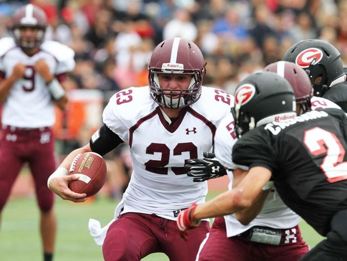 Harrison's Zach Evans (23) finds some running room in the Rye defense during the annual Rye-Harrison game at Rye High School Sept. 13, 2014. Rye won the game 24-13.
