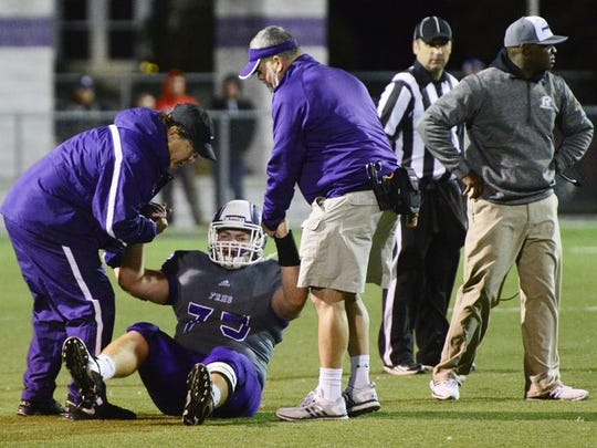 Fremont Ross senior Evan LeJeune is helped up after suffering an injury against Toledo Central Catholic Friday. The Little Giants lost 69-7.