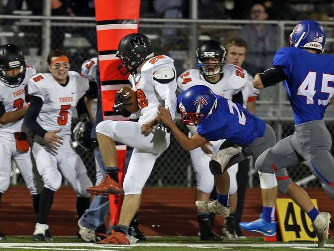 Mamaroneck's Emerson Genovese tries to break free from a Carmel defender on Oct. 16, 2015 at Carmel High School. Mamaroneck won 42-28.