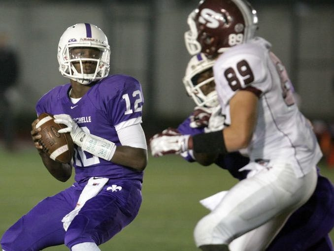 New Rochelle's Greg Powell (12) looks for an open man during football game action against Scarsdale at New Rochelle High School on Oct. 11, 2014.