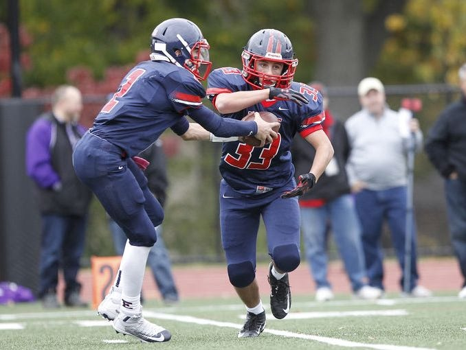 Eastchester quarterback John Archidiacono (2) hands off to John Guido (33) during a varsity football game against John Jay Cross River at Eastchester High School on Saturday, Oct. 24, 2015.
