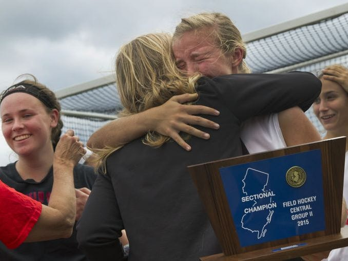 An emotional Michaela Thompson of Wall is hugged as she holds her team's Group Trophy. Wall Field Hockey defeats Rumson-Fair Haven in Girls NJSIAA Central Group II Final at Wall High School in Wall, NJ
