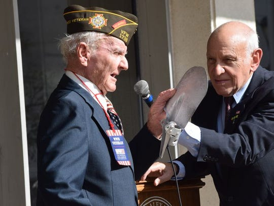 Rabbi Arnold Task (right) holds a microphone while World War II veteran Herbert St. Romain talks about his wartime experiences during a Veterans Day ceremony Wednesday. St. Romain is holding a shovel used to dig foxholes to protect from enemy artillery.