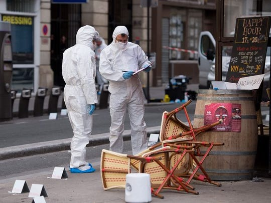 Police forensic experts work on the scene of one of the shootings that took place in Paris at the Cafe Comptoir Voltaire in Paris on Nov. 14, 2015.