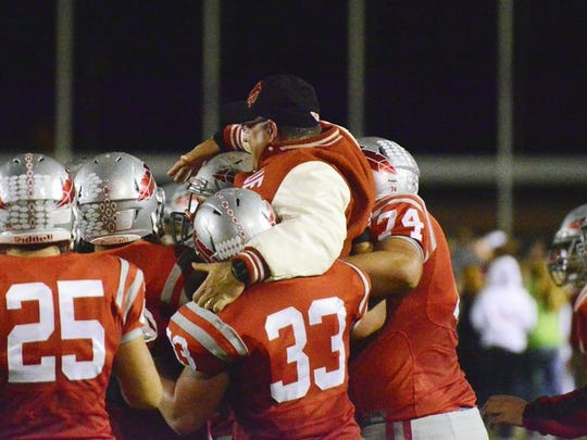 The Bellevue football team carries coach Ed Nasonti following the Redmen's victory over Shelby.