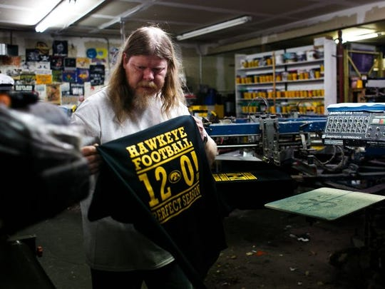 Chris Clifton prints T-shirts at the Strawberry Patch in Ankeny commemorating the Iowa Hawkeyes 12-0 season.