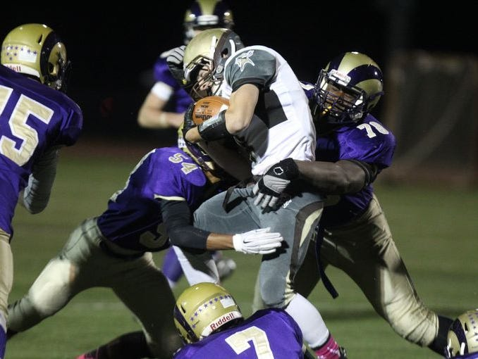 Cameron Conrad (54) and Prince Emili (78) meet at the ball carrier during Clarkstown North's 21-0 defeat of rival Clarkstown South in the Class AA quarterfinals on Oct. 23, 2015.