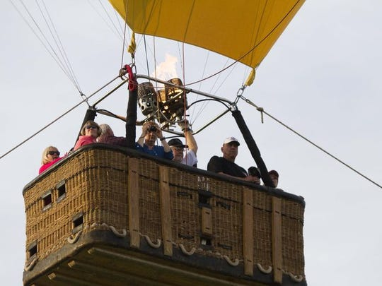 Captain Mike England takes passengers up on a tethered balloon ride during the Arizona Balloon Classic at the Fear Farm Sports & Entertainment Complex on Friday, Jan. 23, 2015, in Phoenix.