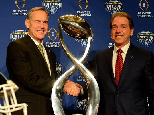Nick Saban, right, and Mark Dantonio, left, pose with the Cotton Bowl trophy before their College Football Playoff matchup in 2015.