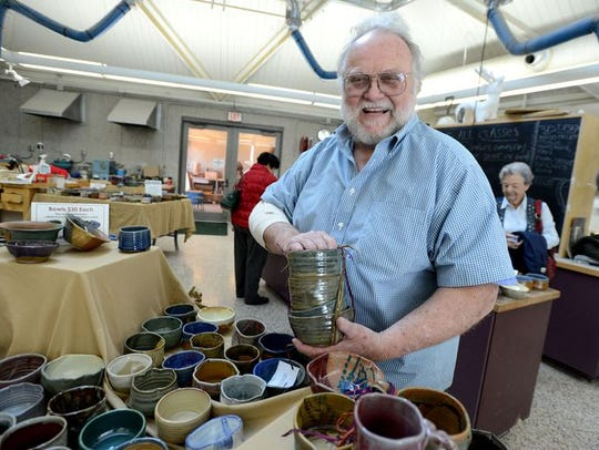 Bill Clover, a beloved art professor at Pensacola State College who died in May, shows off some of the bowls to be sold during a previous Pick A Bowl Fill A Bowl.