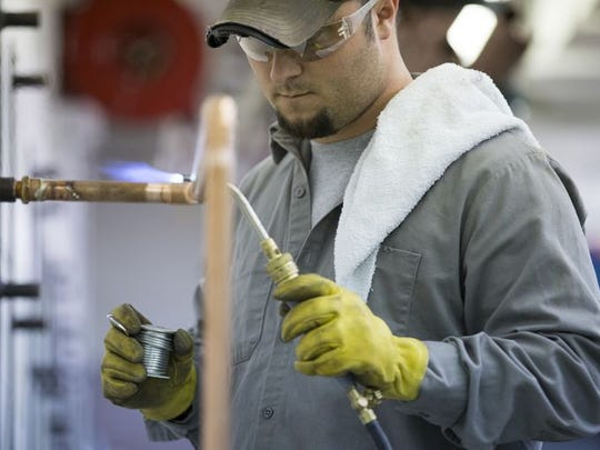 Brett Stephenson, Clayton, solders copper piping in the training center at Plumbers Local 440 in Indianapolis.