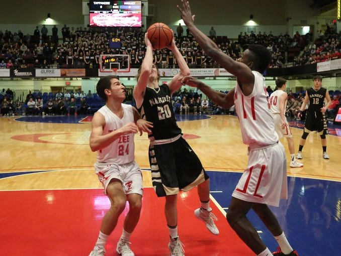 Nanuet's Terence Rogers tries to slip between Tappan Zee's Robert McWilliams (left) and Victor Clervil on his drive to the basket during Tappan Zee's 53-40 victory in the Class A semifinals at the Westchester County Center on Feb. 22, 2016.