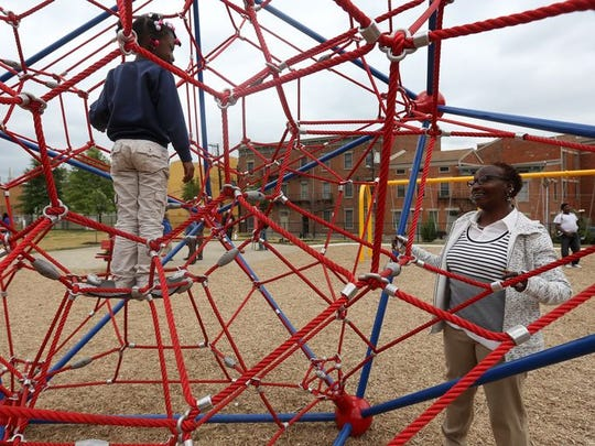 Angela Merritt, of Over-the-Rhine, watches her daughter, Aphenatee, play on new equipment in Grant Park. It was one of two Cincinnati Neighborhood Enhancement Program projects last year. The first project of 2016 begins today in Lower Price Hill.