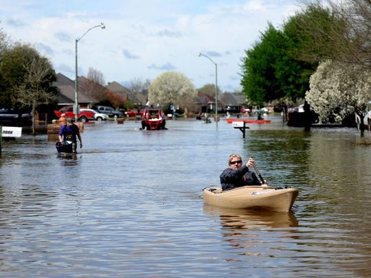Golden Meadows resident Sabrina Langley canoes to the road to leave the flooded subdivision in Bossier City, Louisiana Thursday afternoon, March 10, 2016.