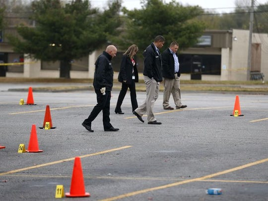 Detectives look for evidence in the parking lot of
