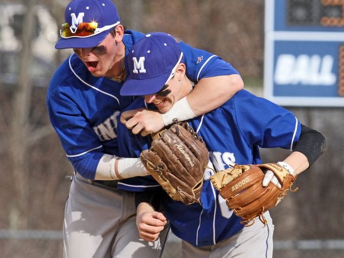 Mahopac second baseman Brendan White, right, is congratulated by teammate CJ Sager after making a bare handed putout in the third inning of a varsity baseball game against Carmel at Mahopac High School April 15, 2015. Mahopac defeated Carmel 8-0.