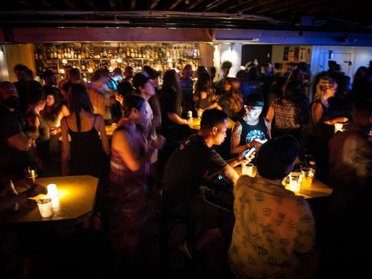 The darkness of the ballroom is illuminated by candles during Blunt Club at Valley Bar in Phoenix on Thursday, July 24, 2015.