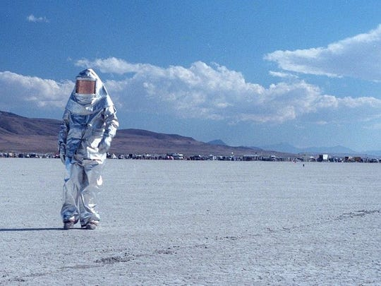 A Burning Man participant walks around in a reflective, astronaut-like suit during the 1999 event in the Black Rock Desert.