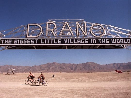 "Bicyclists at the 1998 Burning Man event ride beneath a ""Drano"" sign mocking the ""Biggest Little City in the World"" sign in Reno."