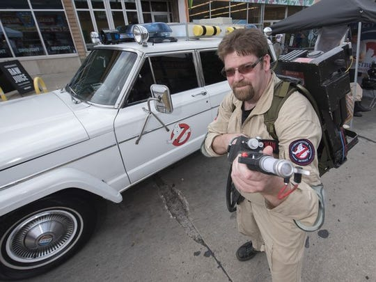 "Mike Dockeray of Warren is dressed as Peter Venkman from the movie ""Ghostbusters,"" as he stands in front of a 1977 Wagoneer owned by Eric Milkman of Sterling Heights."