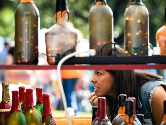 Morgan Fletcher of Evansville selects decorative bottle at Lions Club Arts and Crafts Fest in Audubon State Park in early October.