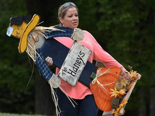 Tara Haney of Hanson takes a scarecrow to her car during