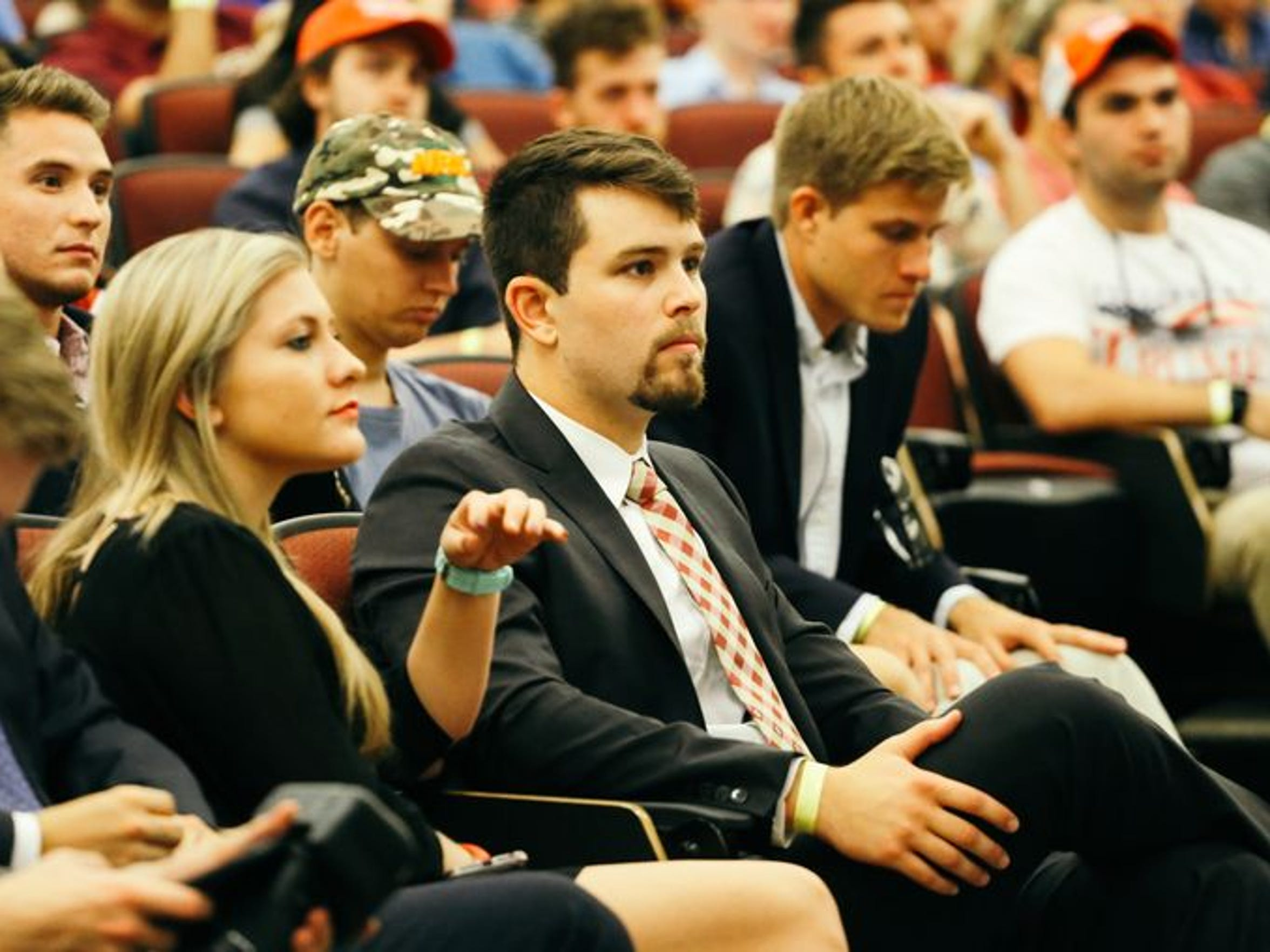 James Dilmore, president of the College Republicans, watches as Milo Yiannopoulus speaks on campus.