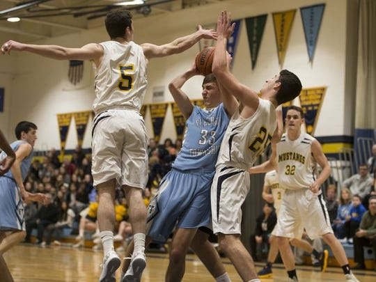 Freehold Township's Ryan Zyskowski (33) grabs a rebound between Marlboro's P.J. Ringel (5) and Justin Marcus (25) during a game on Feb. 7, 2017.